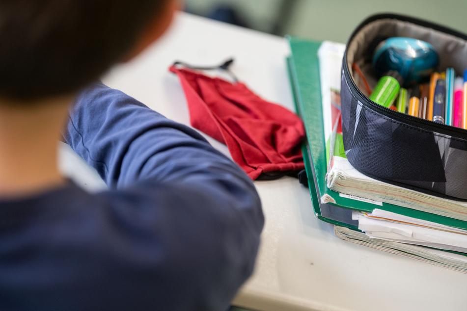 Eine Mund-Nasen-Bedeckung liegt während einer Unterrichtsstunde einer fünften Klasse des Friedrich-Schiller Gymnasiums neben einem Mäppchen und Schulbüchern auf einem Schultisch.