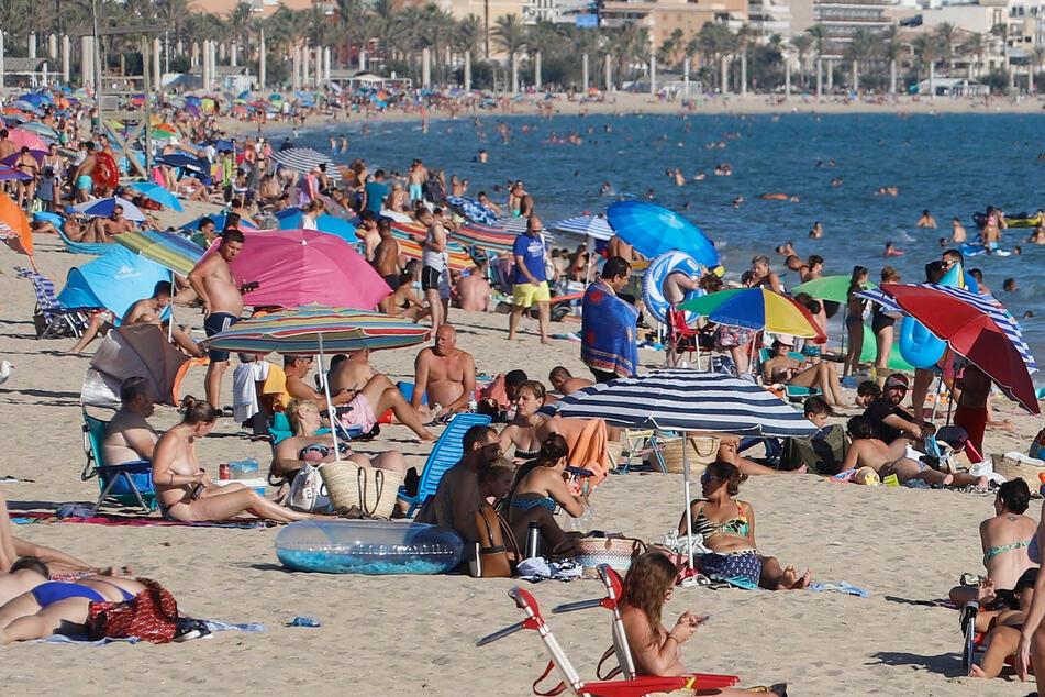 Spanien, Palma de Mallorca: Menschen genießen die Sonne am Strand von El Arenal. (Symbolbild)