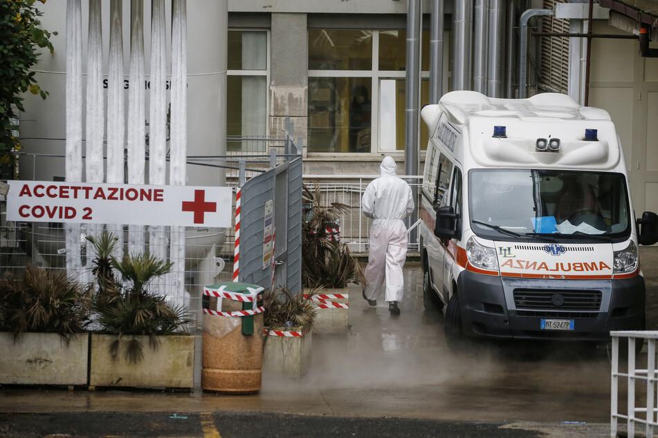 """Ein medizinischer Mitarbeiter trägt einen Schutzanzug und geht neben einem Krankenwagen vorbei am Eingang des ambulantem Bereich des """"Agostino Gemelli"""" Krankenhauses in Rom."""