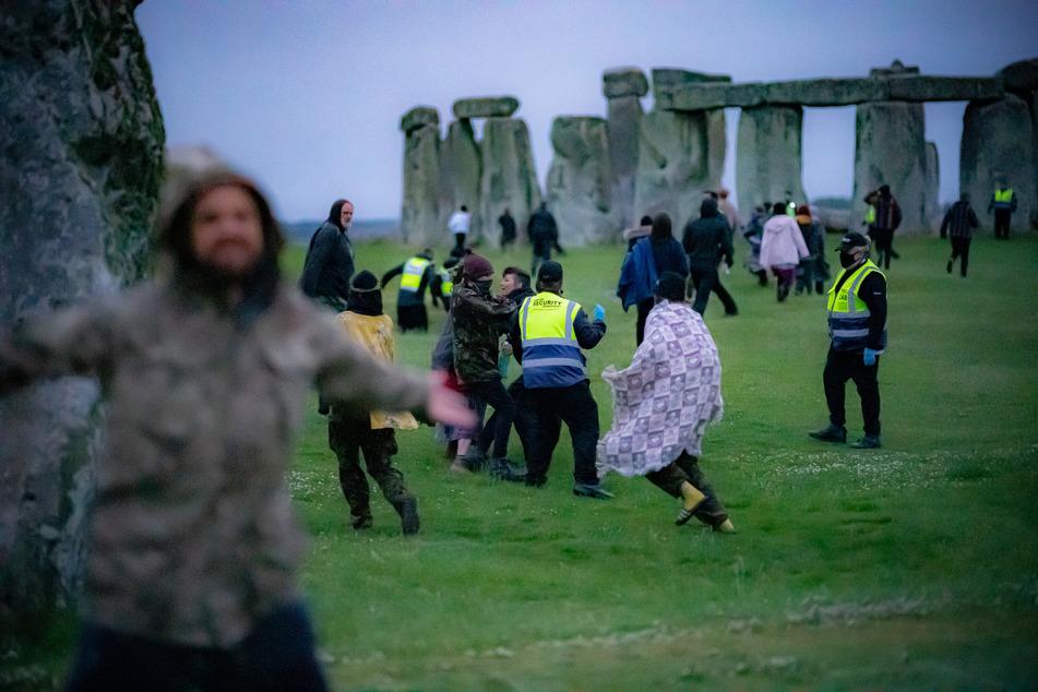 Menschen sprangen in den frühen Morgenstunden über einen Zaun und bahnten sich ihren Weg an Sicherheitspersonal vorbei in Richtung Stonehenge.