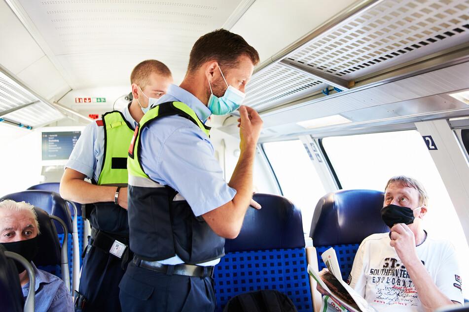 Mitarbeiter der DB Sicherheit und Beamte der Bundespolizei gehen durch einen Zug und kontrollieren, ob alle Reisenden ihre Masken korrekt tragen.