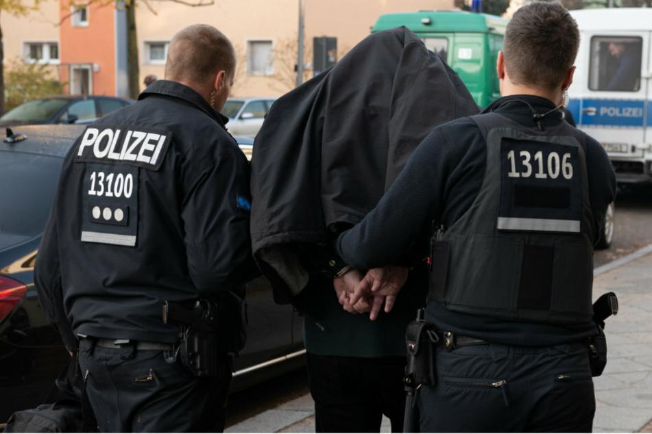 Polizeibeamte führen einen festgenommenen Mann nach einer Razzia im Kampf gegen kriminelle Mitglieder von arabischstämmigen Clans ab. (Archivbild)