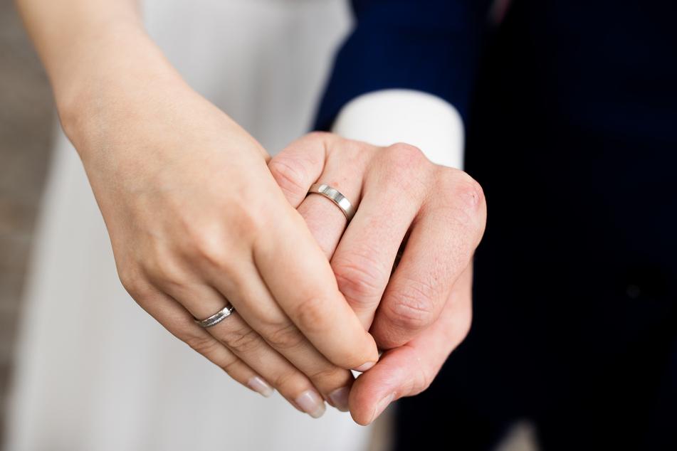 Ein frisch vermähltes Brautpaar zeigt nach der Eheschließung im Rathaus die Eheringe.