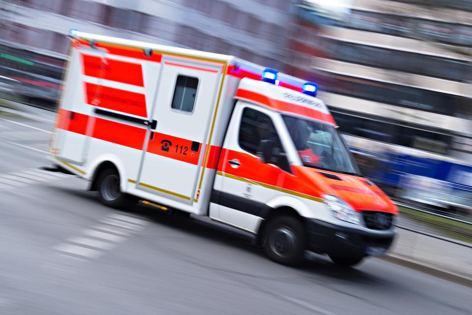 Ein Rettungswagen mit der Aufschrift 112 fährt mit Blaulicht durch die Stadt.