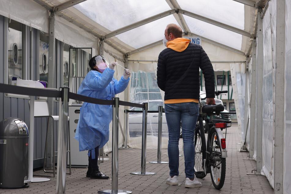 Mit seinem Fahrrad kommt ein Passant zum Fahrrad-Drive-In zum Schnelltesten in Hamburg-Eimsbüttel.