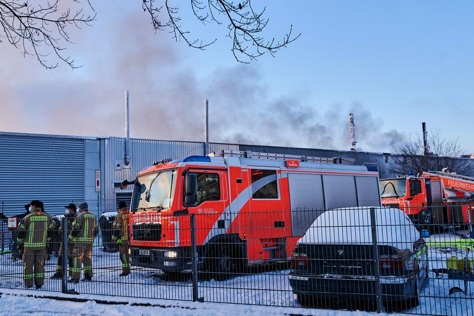 Feuerwehrmänner und Wägen stehen vor der Halle in Marienfelde.