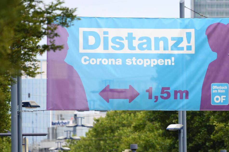 """Ein großes Plakat mit der Aufschrift """"Distanz! Corona stoppen!"""" prangt am Ortseingang von Offenbach über einer Straßenkreuzung."""