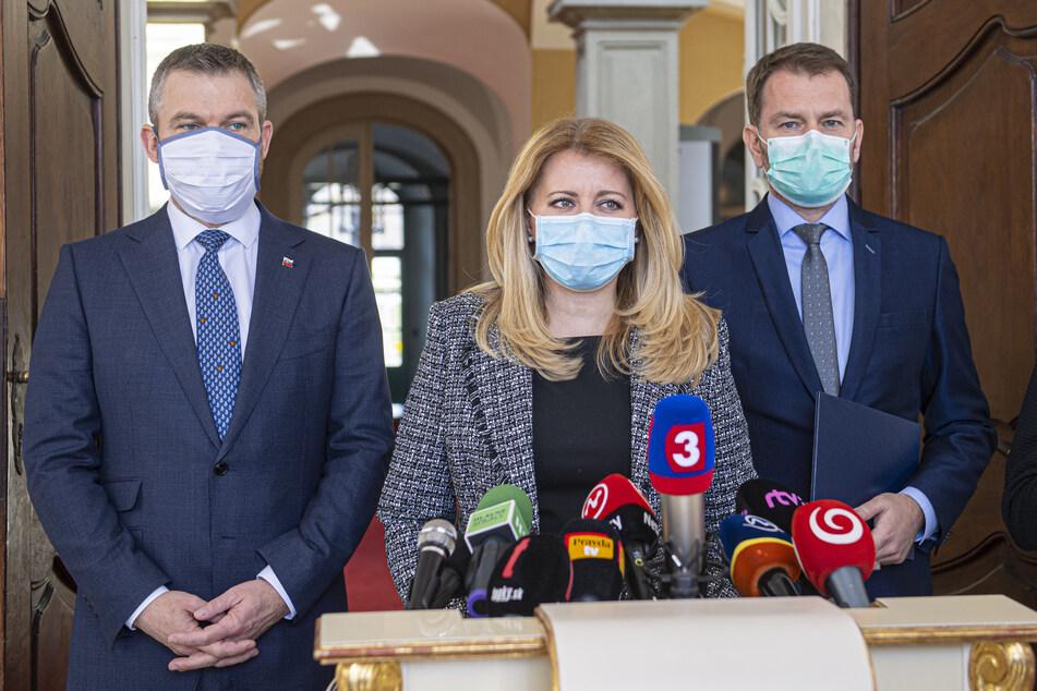 Zuzana Caputova (M), Präsidentin der Slowakei, Peter Pellegrini (l), der scheidende Premierminister der Slowakei und Igor Matovic, Abgeordneter des Nationalrats und potenzieller Nachfolger von Pellegrini tragen während einer Pressekonferenz Mundschutzmasken.