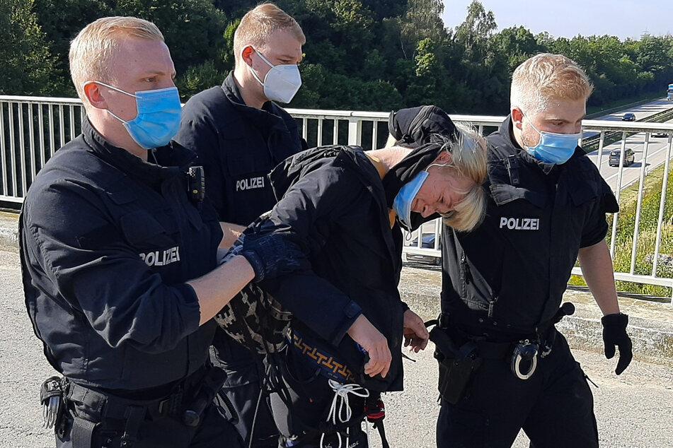 Eine Aktivistin wird von der Polizei abgeführt.