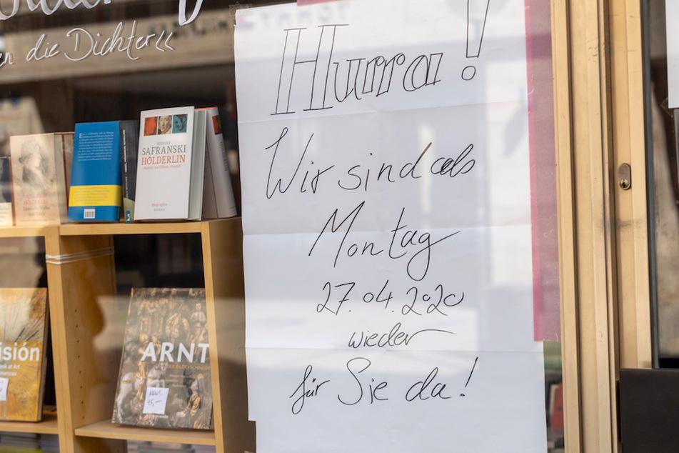 """Ein Schild mit der Aufschrift """"Hurra! Wir sind ab Montag 27.04.2020 wieder für Sie da!"""" hängt in der Tür zu einem Geschäft in der Münchner Innenstadt."""
