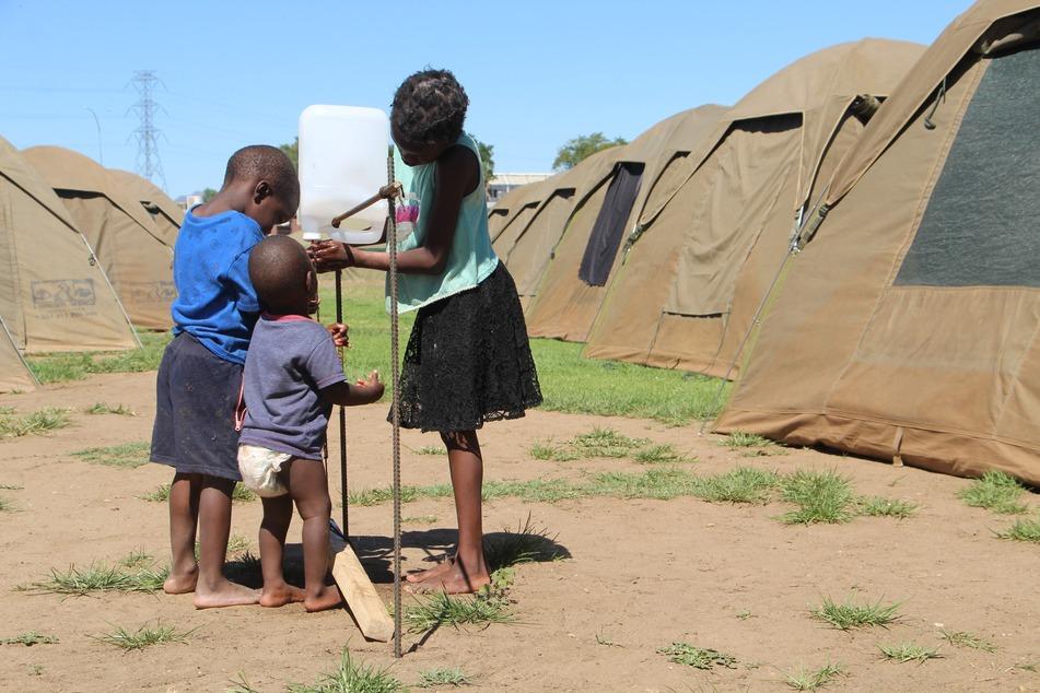 Kinder waschen sich an einer Notunterkunft in Namibia die Hände. Fließendes Wasser gibt es hier nicht.