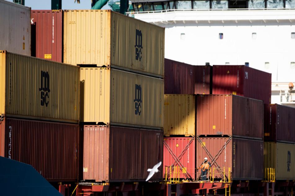 Ein Arbeiter mit einer Mundmaske steht in der Nähe von Containern auf einem Schiff im Hafen.