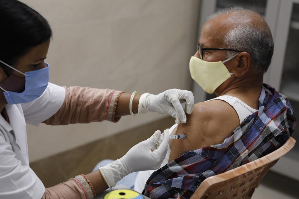Ein älterer Mann wird in der medizinischen Hochschule Moti Lal Nehru gegen das Coronavirus geimpft.