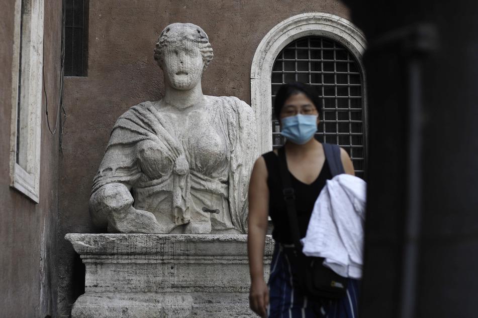 Rom: Eine Passantin mit Mundschutz geht an einer antiken römischen Büste vorbei, die vor einem Gebäude auf einem Sockel thront.