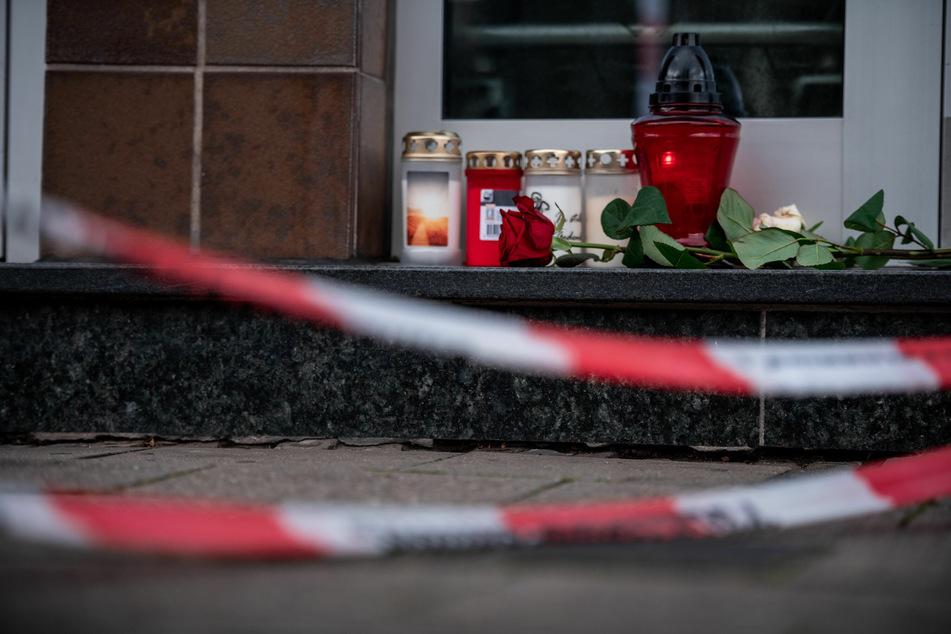Der Eingang eines Hauses ist mit Flatterband der Polizei abgesperrt, Rosen und Kerzen wurden neben die Haustüre gelegt.