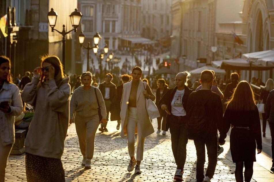 Menschen, die meisten von ihnen ohne Mund-Nasen-Schutz, spazieren bei warmem Wetter während eines Sonnenuntergangs im Zentrum von Moskau.