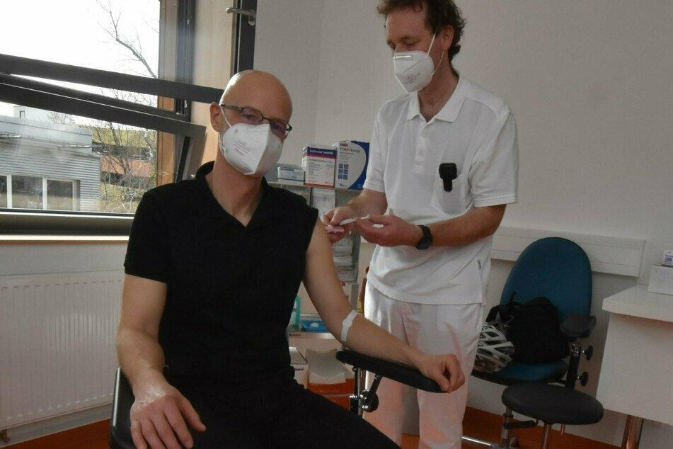 Prof. Gunnar Folprecht (r.), Leiter des Fachbereichs Onkologie des Uniklinikums Dresden, impft Peer Schmidt.