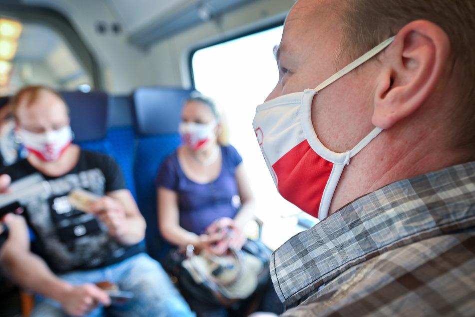 Reisende mit Masken in einem Zug der Deutschen Bahn in Halle. Sieben der 17 neuen Fälle in der Stadt sollen laut OB Wiegand auf Busreisen, Urlaub oder Besucher aus dem Ausland zurückzuführen sein.