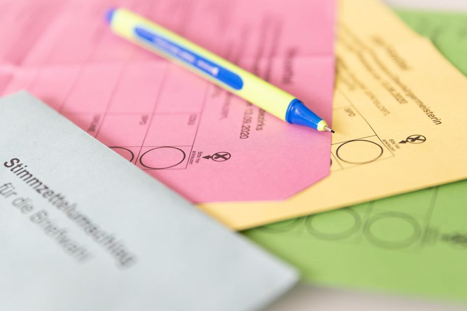 Verschiedene Stimmzettel und ein Stimmzettelumschlag für die Briefwahl liegen auf einem Tisch zusammen mit einem Stift.