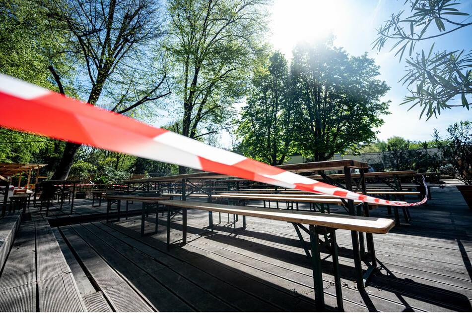 Ein rotes Band sperrt in einem geschlossenen Biergarten im Tiergarten den Außenbereich ab.