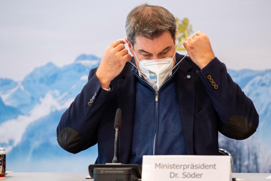 Markus Söder (CSU), Parteivorsitzender und Ministerpräsident von Bayern, nimmt zu Beginn einer Sitzung des Ministerrats in der Staatskanzlei seine FFP2-Schutzmaske ab.