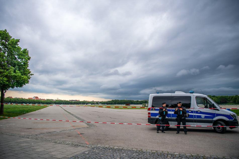 Polizisten sperren die Theresienwiese ab. Am Horizont sind Dunkle Wolken zu sehen.