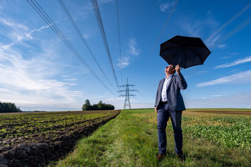 Josef Klaus, Bürgermeister von Niederaichbach, steht mit einem Regenschirm unter der problematischen Hochspannungsleitung.