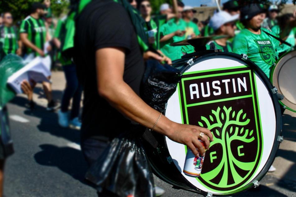 Austin FC fans march to Q2 stadium alongside La Murga de Austin on game day.