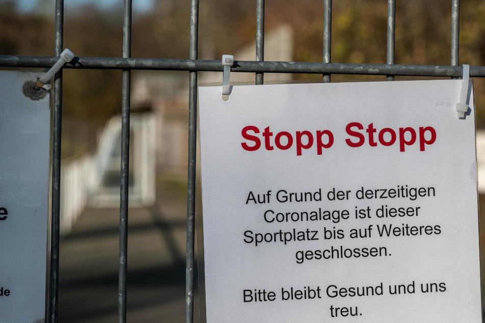 """Ein Schild mit der Aufschrift """"Stopp Stopp"""" hängt am Zaun des Fußballplatzes. Die Corona-Pandemie hat den Vereinssport stark getroffen. Gemeinsame Trainingseinheiten sind seit Monaten verboten."""