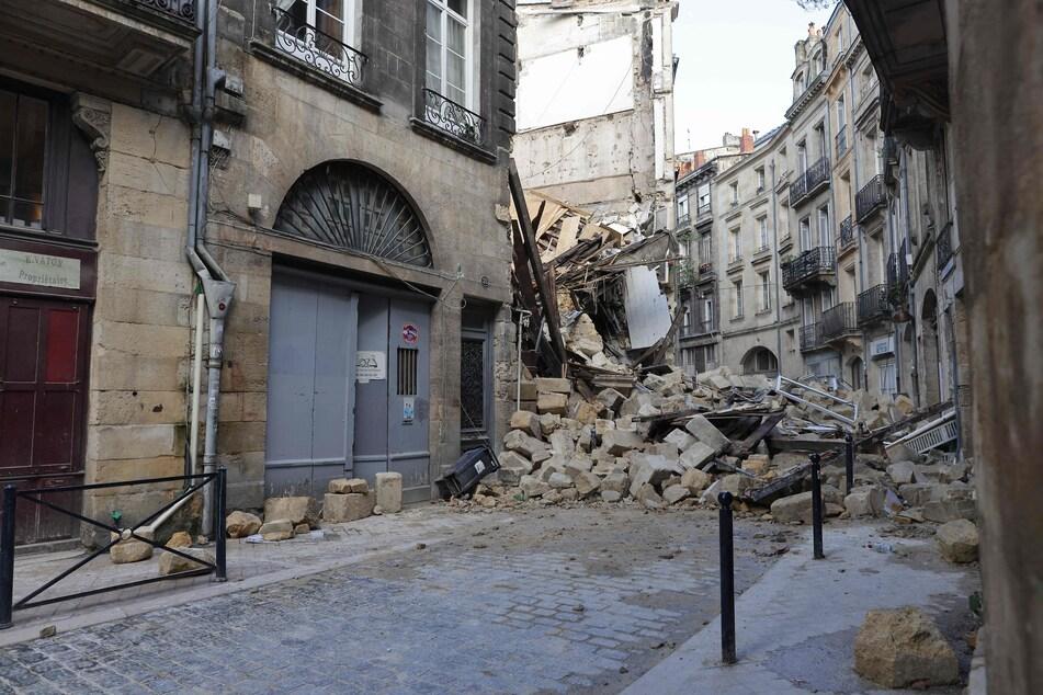 Trümmer von den zwei eingestürzten Häusern liegen auf einer Straße in der Altstadt von Bordeaux.