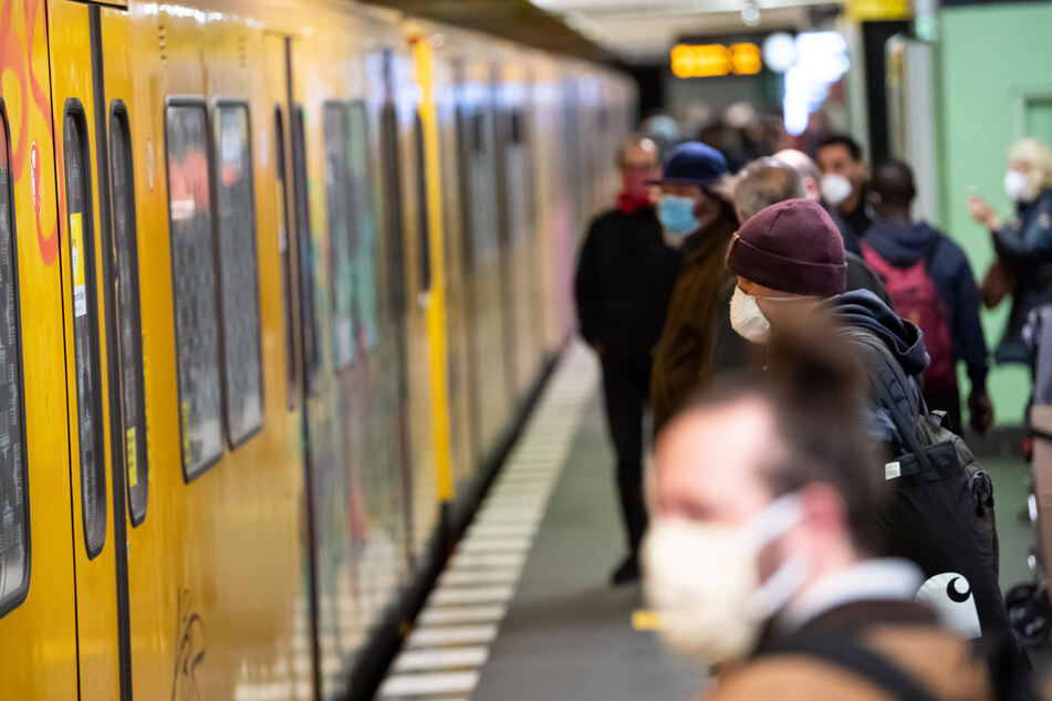 Fahrgäste mit Mund-Nasen-Schutz stehen auf dem U-Bahnhof Französische Straße in Berlin-Mitte neben der eingefahrenen U-Bahn.