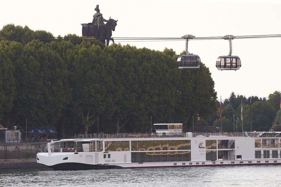 Ein Flusskreuzfahrtschiff liegt am Rheinufer in Koblenz unterhalb des Deutschen Ecks mit dem Reiterstandbild von Kaiser Wilhelm.