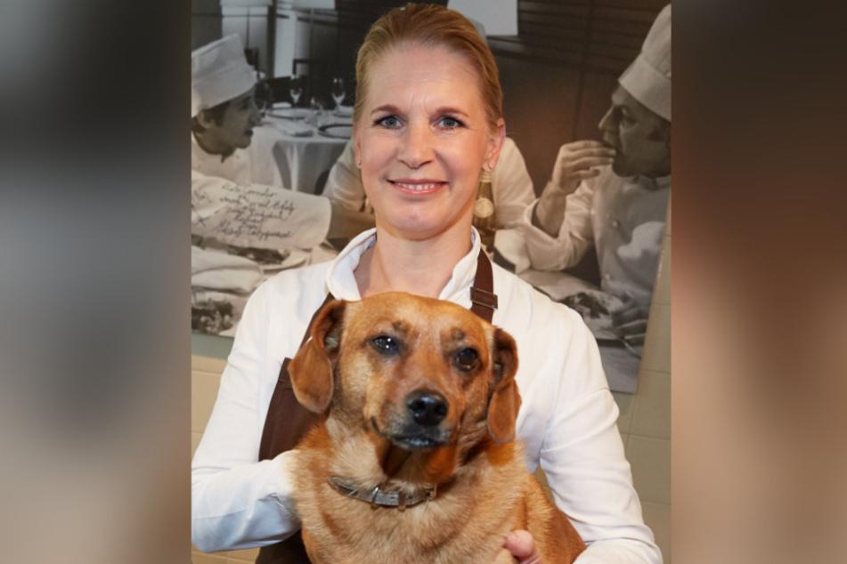 Die Spitzenköchin Cornelia Poletto steht während eines Pressetermins neben ihrem Hund Franz.