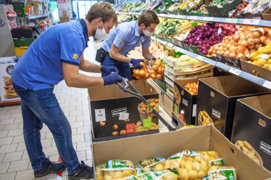 Arbeit in Zeiten der Corona-Krise: Kevin Krawietz (l.) räumt in einem Discounter Kartoffeln neben dem Filialleiter Mirnis Terzic (r.) in ein Regal ein.