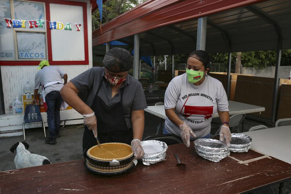 Freiwillige Helfer schneiden Kürbiskuchen in Portionen, um sie für ein Thanksgiving-Essen für Obdachlose und Bedürftige der Gemeinde in Behälter zu füllen.