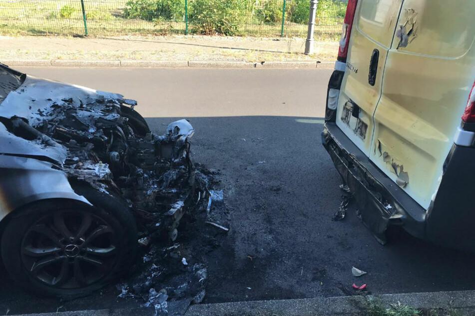Der ausgebrannte Mercedes in der Winterstraße in Berlin Reinickendorf. Davor der beschädigte Renault Transporter.