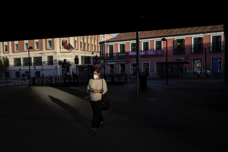 Eine Frau mit Gesichtsmaske trägt geht über einen leeren Platz in Madrid.