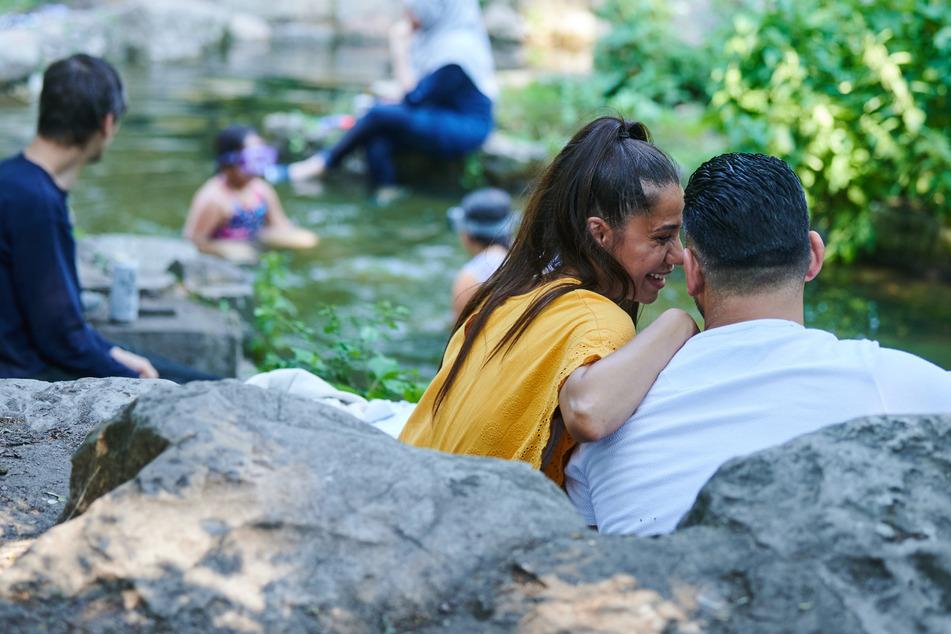 Im Viktoriapark sitzt ein Pärchen am Wasserfall während sich andere Menschen im Wasser abkühlen. Ab Dienstag erreichen die Gewitter auch Berlin.