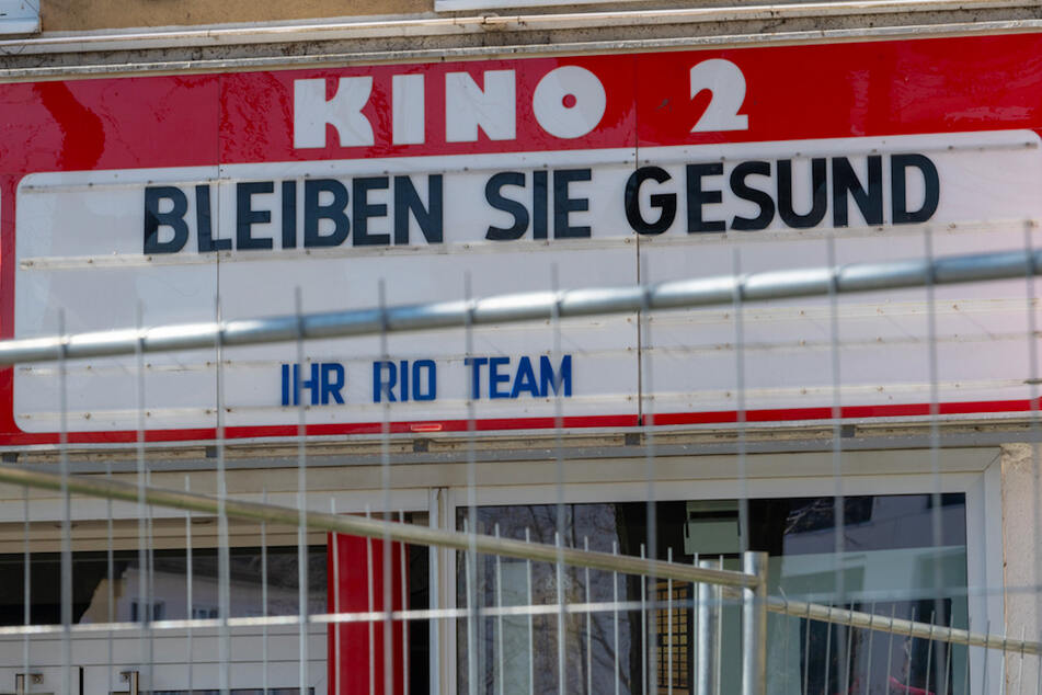 """""""Bleiben sie Gesund"""" steht über dem Eingang eines geschlossenen Kinos im Münchner Bezirk Haidhausen. Normalerweise stehen hier die aktuellen Kinofilme."""