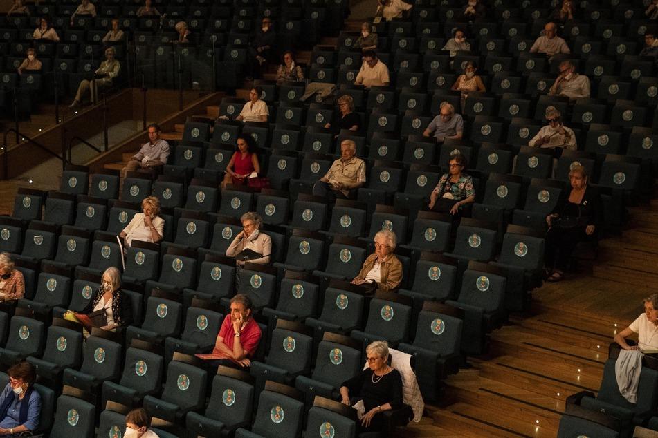 Zuschauer sitzen unter Mindestabstand in einem Theater. (Symbolbild)