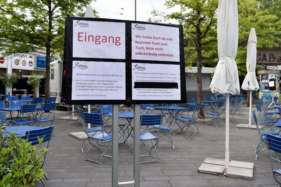 Ein Schild erklärt den Gästen das Verhalten während der Corona-Beschränkungen im Biergarten im Bermunda3Eck in Bochum.