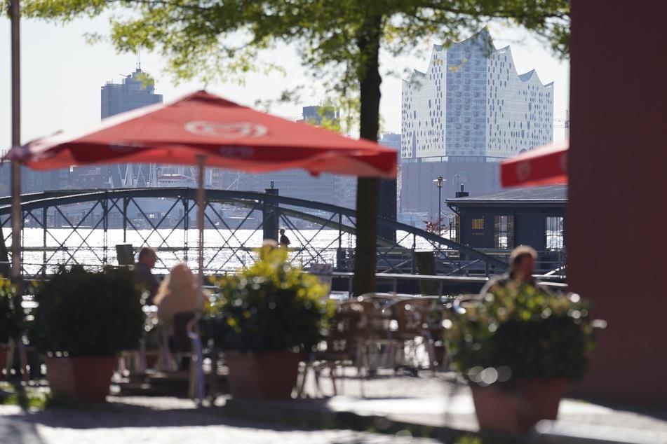 Kunden genießen die Sonne in einem Café am Fischmarkt. Ab dem Wochenende darf auch die Innengastronomie wieder öffnen.