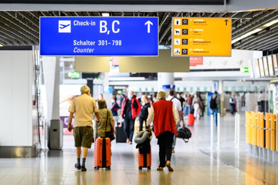 Reisende gehen am Flughafen mit Gepäck durch die Abflughalle im Terminal 1.