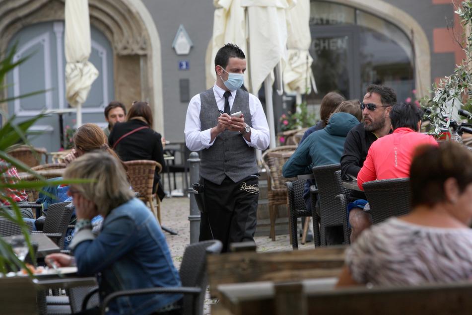 Ein Kellner mit Mundschutz bewirtet die Gäste vor dem italienischen Restaurant La Dolce Vita.