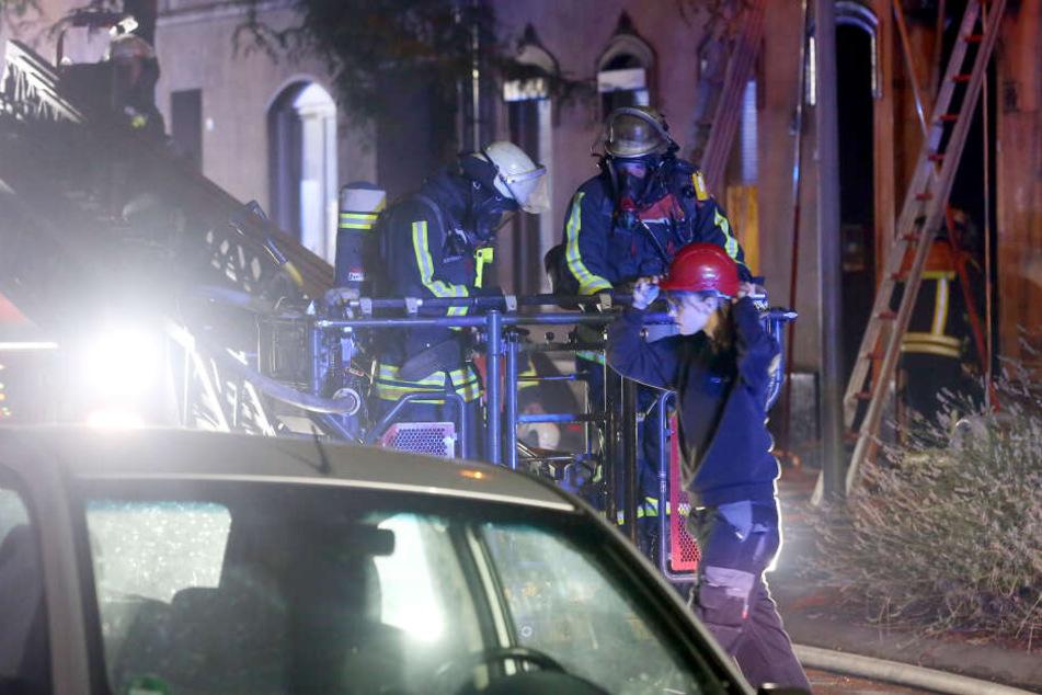 Kameraden besteigen an der Brandstelle einen Löschkorb.