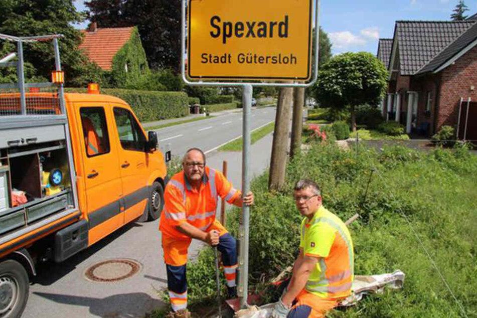 Meinolf Huster (l.) und Martin Hano vom Kreisbauhof sorgen dafür, dass das Schild wieder fest an seinem Platz steht.