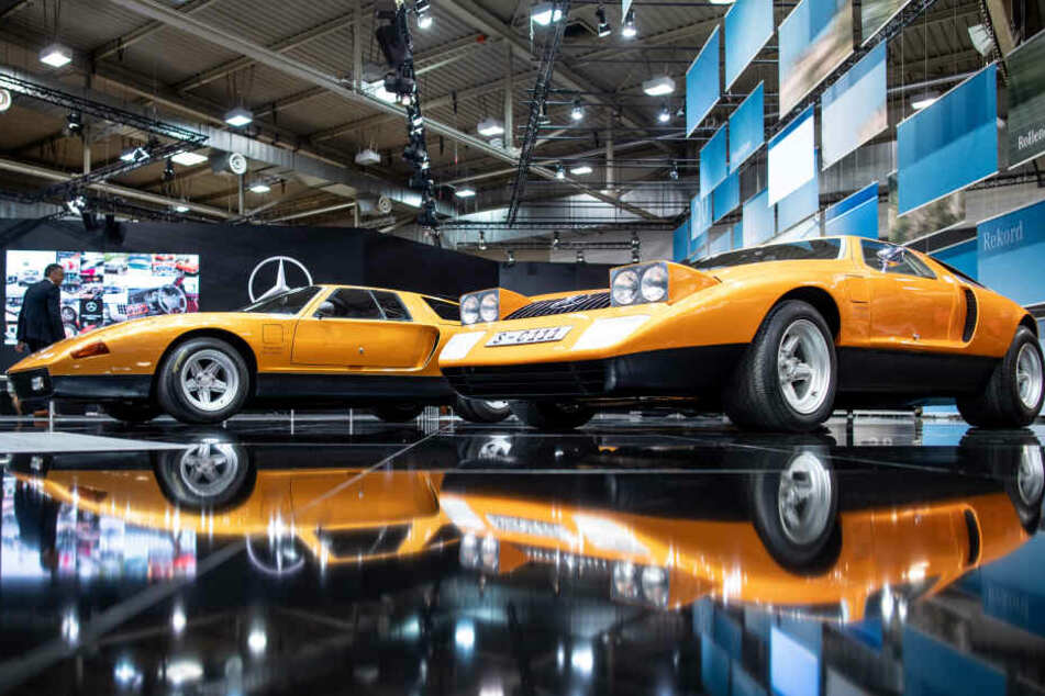 Die beiden Fahrzeuge Mercedes-Benz C111 von 1969 (r) und Mercedes-Benz C111-II von 1970 spiegeln sich bei der Techno Classica für Oldtimer und Youngtimer im Boden.