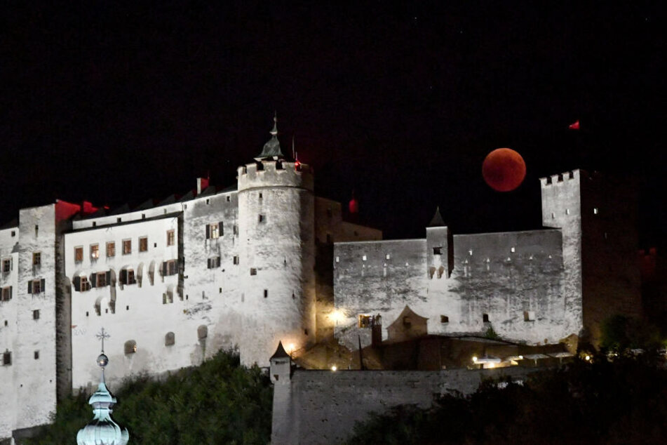Malerische Kulisse: Der Blutmond erhebt sich über der Festung Hohen Salzburg in Österreich.