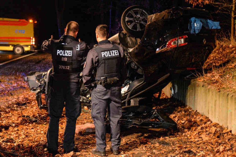 Polizisten betrachten den Unfallwagen.