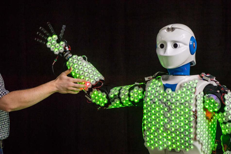 Der Arm eines Wissenschaftlers berührt einen humanoiden Roboter.
